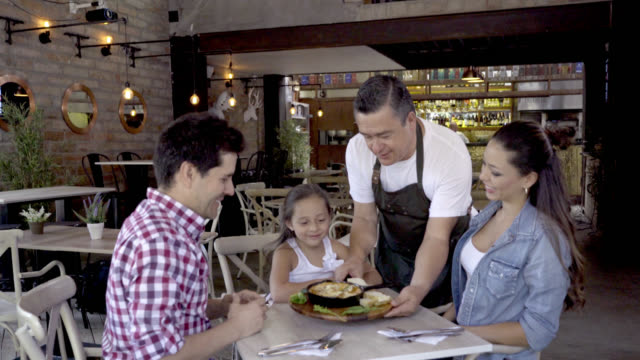 Family having fun at a restaurant while happy waiter serves an appetiser