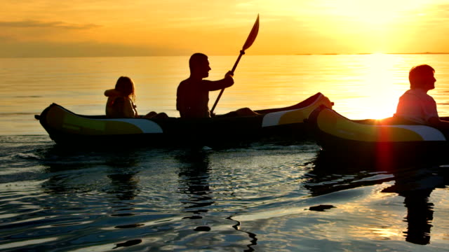 TS Family Having Fun Sea Kayaking At Sunset