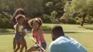 Family having tug of war in park