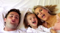 Family Hiding Under Sheet In Bed