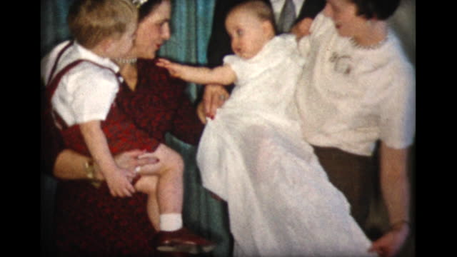 1957 family holding 10 month old girl in long, white baptismal dress