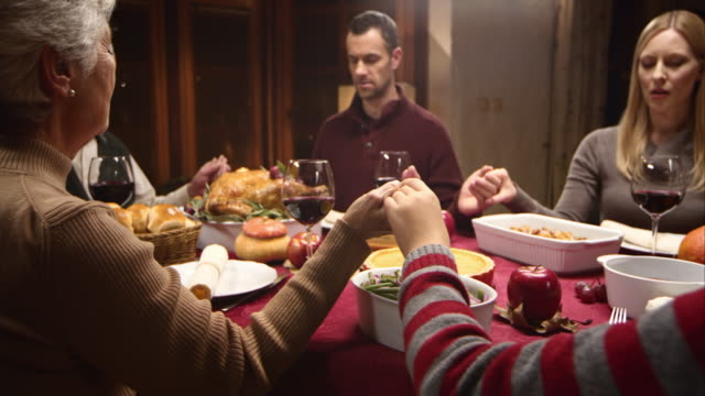 Family holding hands at Thanksgiving table and grandmother saying grace