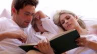 Famiglia leggendo un libro insieme a letto