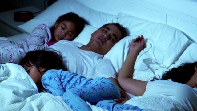 Family in bed together sleeping
