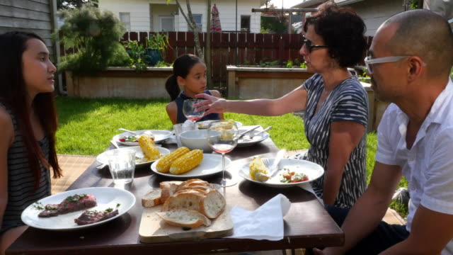 MS ZI Family in discussion while eating dinner in backyard on summer evening