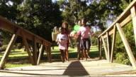 Family in park running across bridge