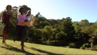 Family in Park running with ball