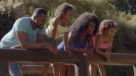 Family in park standing on wooden bridge over stream