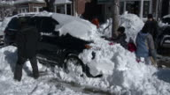 A family in Queens NY digs their vehicle out from under deep snow in the aftermath of the Blizzard of 2016