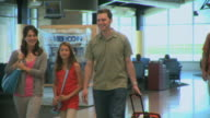 MS Family including girl (8-9) walking through airport, Appleton, Wisconsin, USA