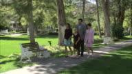 WS PAN Family including two girls (11-17) walking through park / Heber City, Utah, USA