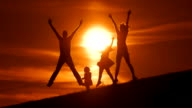 HD SLOW MOTION: Family Jumping For Joy At Sunset