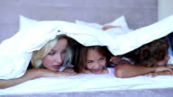Family lying under the covers and chatting