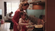 Family making pancakes in kitchen at home