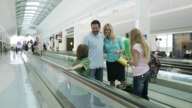 MS POV Family moving walkway in airport  / Jacksonville, FL, United States