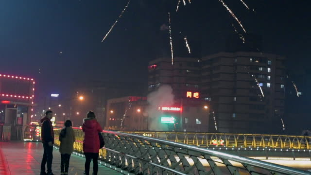 A family of 4 watches the fireworks atop a large pedestrian overpass