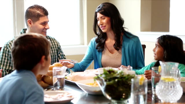 Family of four enjoying dinner together at home