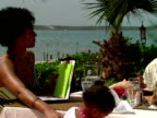 MS,  PAN,  family of four sitting at outdoor table in restaurant,  Harbour Island,  Bahamas