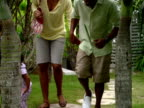 MS,  SHAKY,  family of four walking between palm trees in garden,  Harbour Island,   Bahamas