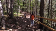 Family of two hiking on pathway through the dense woodland