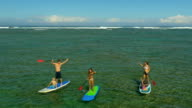 Family paddle boarding on a tropical beach vacation to Hawaii