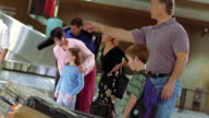 CANTED MS family picking up baggage with other travelers at baggage claim in Phoenix Airport / AZ