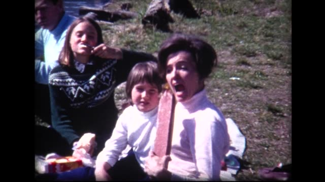1969 family picnic on a lake, mom hams it up with large sausage