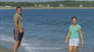 MS PAN Family playing frisbee on beach near water / Phippsburg, Maine, USA