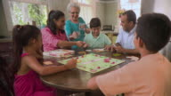 MS Family playing Monopoly game on kitchen table, Panama City, Panama