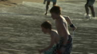 Family playing on beach and in water