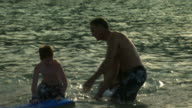 Family playing on beach and in water with belly board