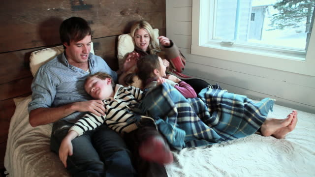 Family playing on bed