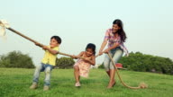 Family playing tug-of-war in the park, Delhi, India