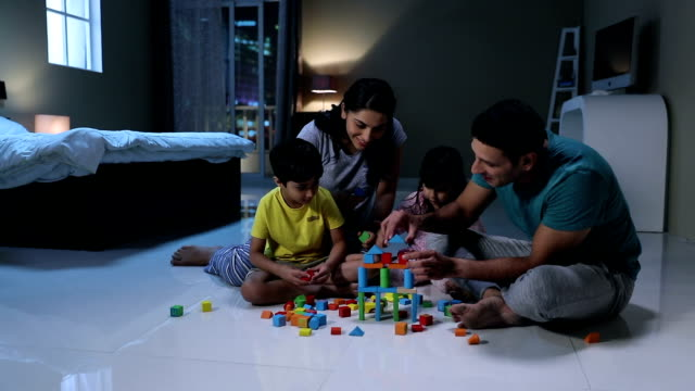 Family playing with building blocks at home, Delhi, India
