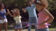 Family playing with hula hoops in park