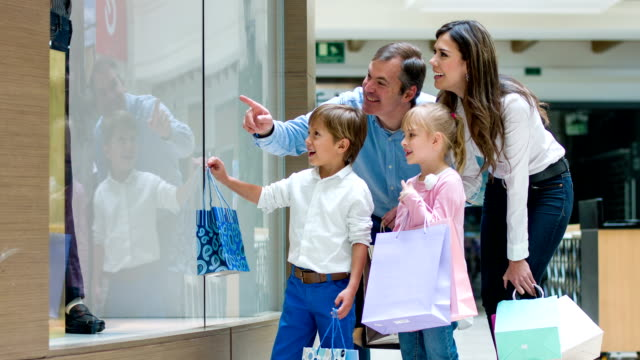 Family pointing at a window at the shopping center