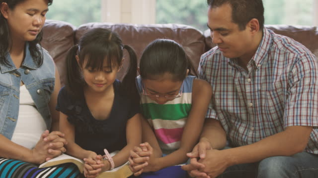 Family praying together during devotionals