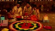 Family preparing rangoli, Delhi, India