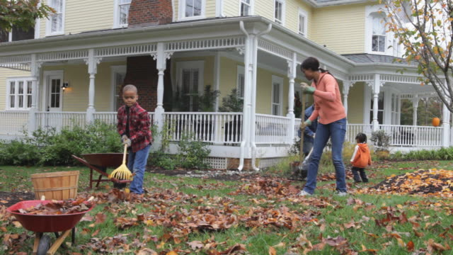 WS Family raking leaves in front yard of home / Richmond, Virginia, USA.