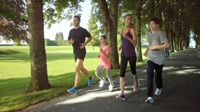 SLO MO TS Family running through tree avenue