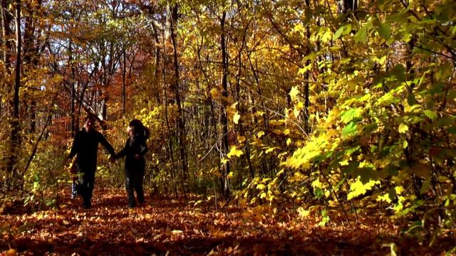 Family Running Through Woods During Autumn in Michigan