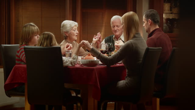 Family saying grace together at the Thanksgiving table before dinner