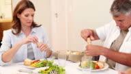 Family seasoning their meal