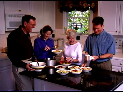 Family serving pasta in kitchen