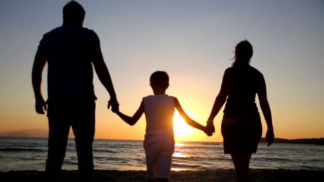 Family silhouettes in sunset