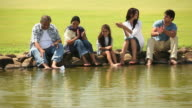 Family sitting at lakeside and floating a paper boat