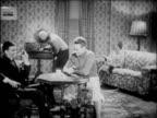 B/W 1927 family sitting in living room listening to radio / newsreel