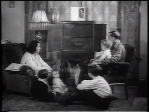 B/W 1934 family sitting in living room listening to radio / newsreel