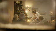 Familie sitzt auf Weihnachten-Tisch