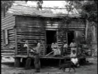 1916 MONTAGE family sitting on the porch of a cabin weaving baskets / Democratic Republic of Congo
